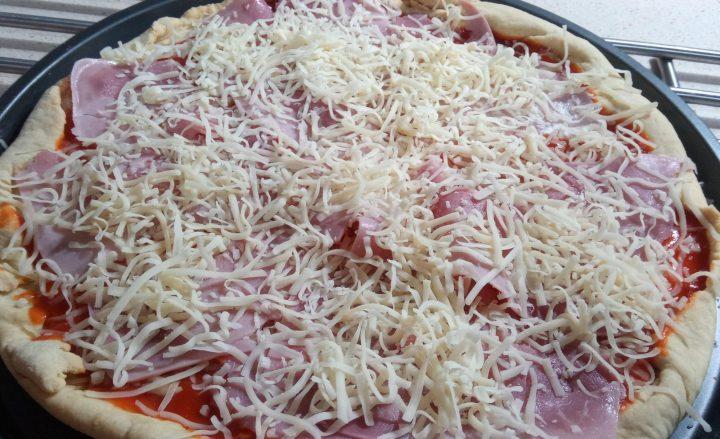 Echar queso y jamón york en la masa de la pizza.