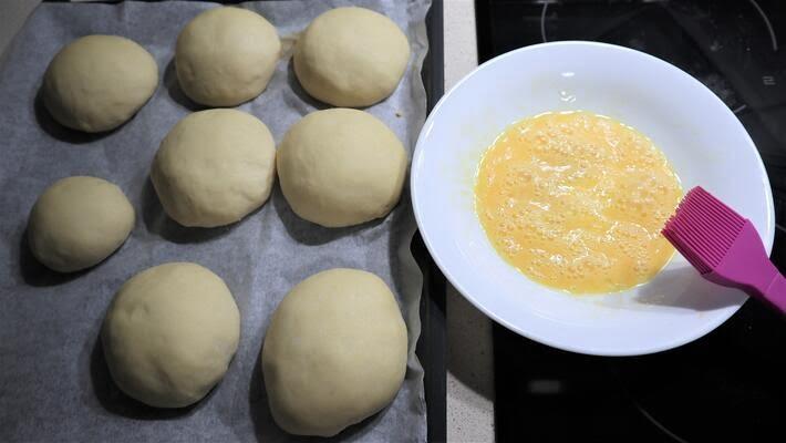 Poner los bollos en una bandeja de horno para pintarlos con huevo y echarle el muesli