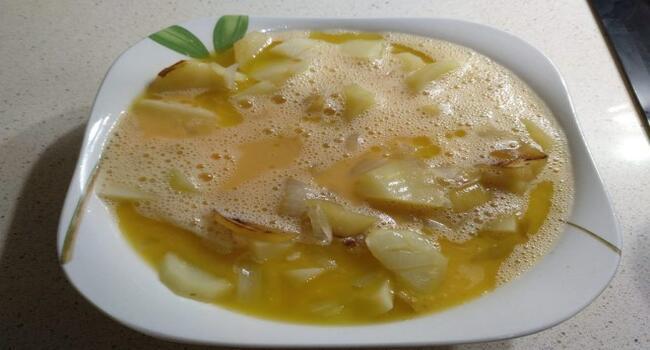 Batimos lo huevos y lo mezclamos con las patatas y la cebolla