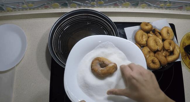 Untar las rosquillas con azúcar